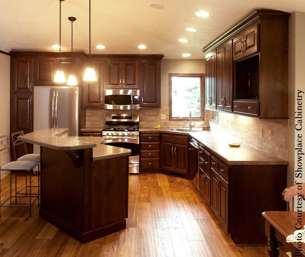G-shaped kitchen layout dark cabinets and stainless appliances