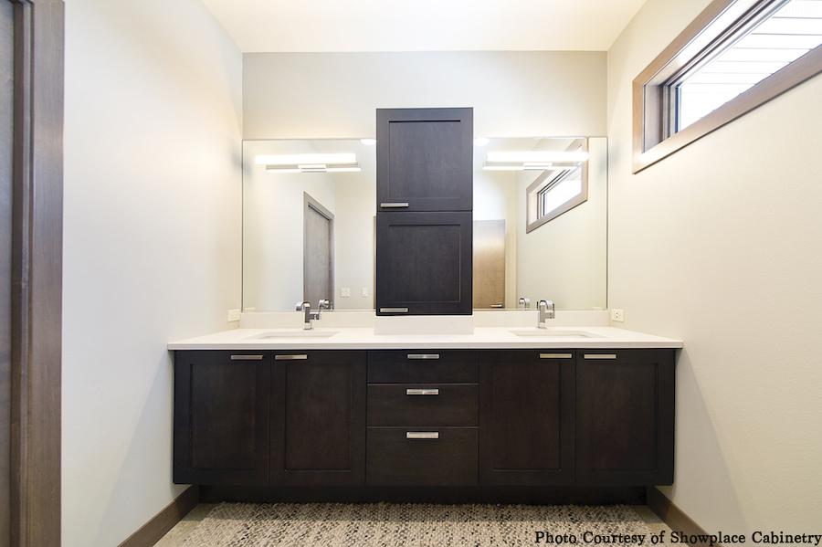 bathroom double vanity, dark cabinets, custom storage for linens, closed
