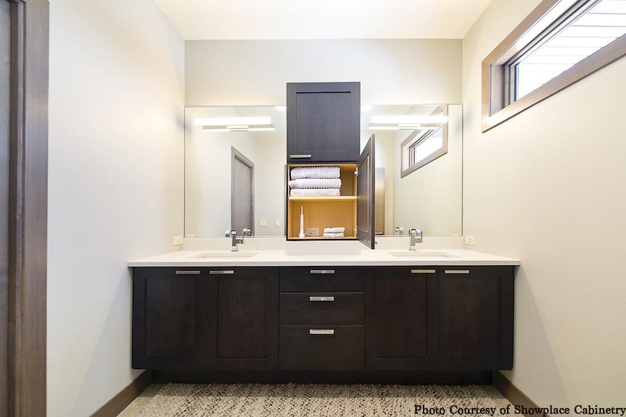 bathroom double vanity, dark cabinets, custom storage for linens, open